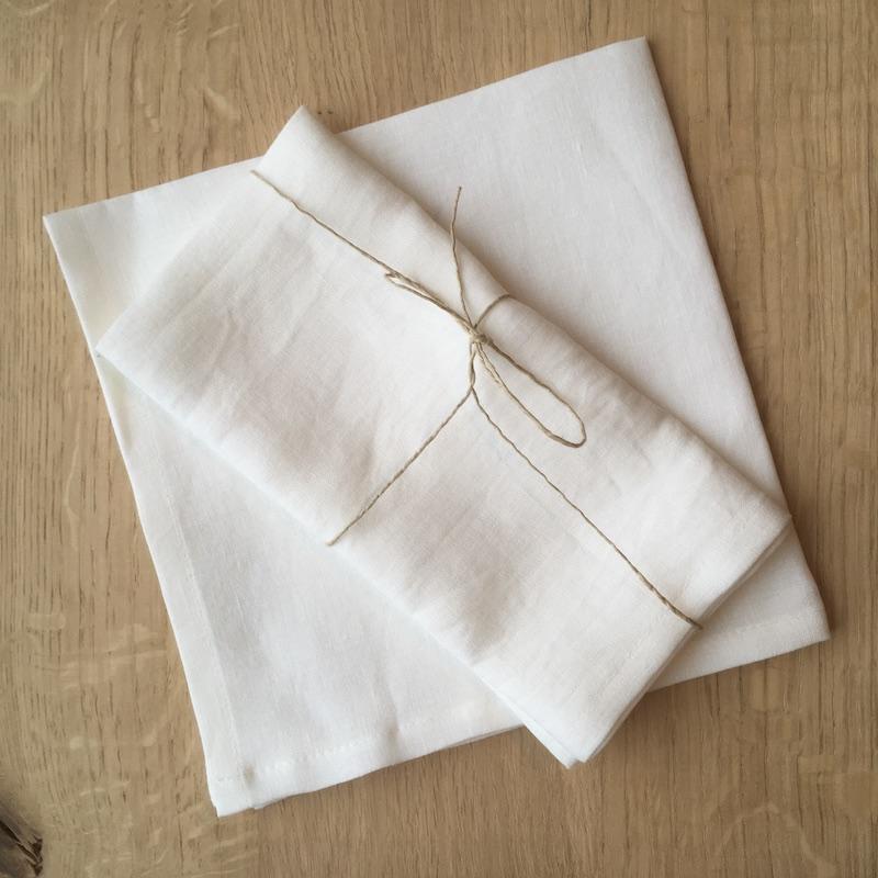zwei weiße Leinen Servietten übereinander gelegt auf Tisch