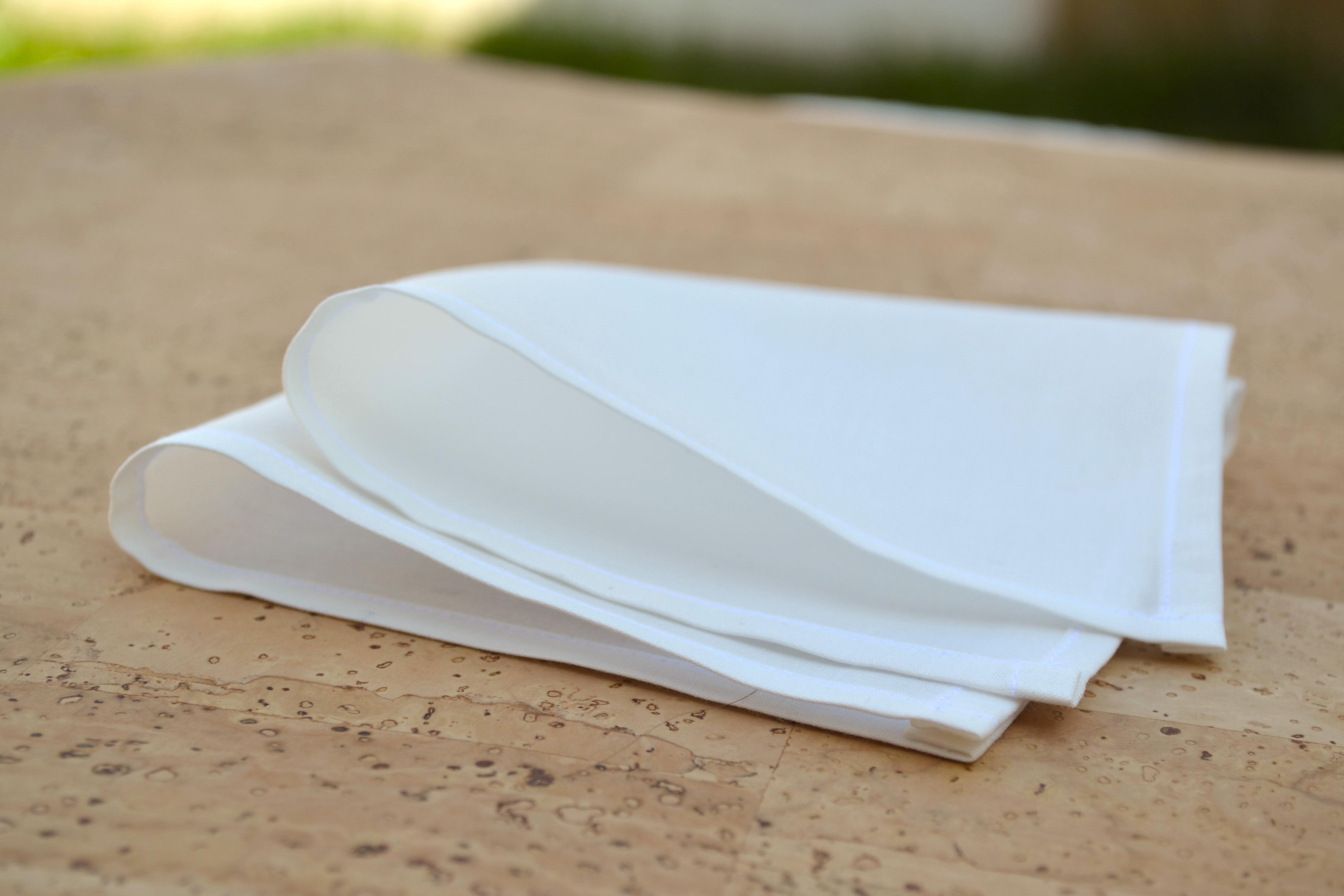 weißes Stofftaschentuch aus Bio Baumwolle, gefaltet auf Kork Tisch