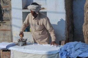 Mann, der Stoffe auf einem Bügelbret mit Volldampf bügelt