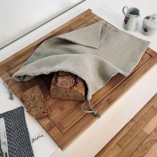 Brotbeutel aus Leinen auf Holzbrett mit Brotlaib