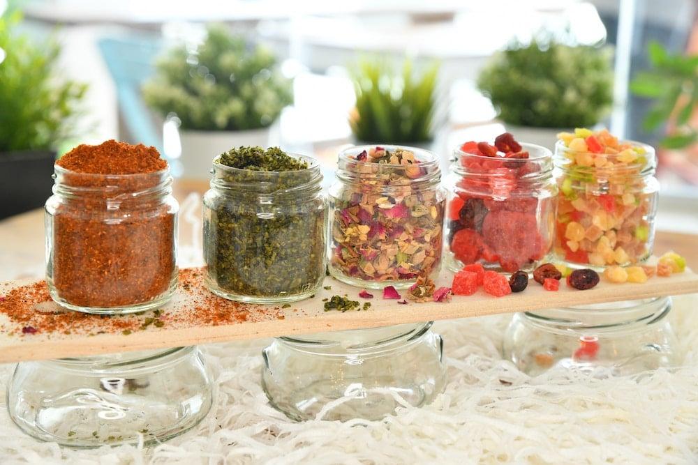4 upgecyclete Gurkengläser stehen nebeneinander und sind mit Gewürzen und Süßigkeiten befüllt