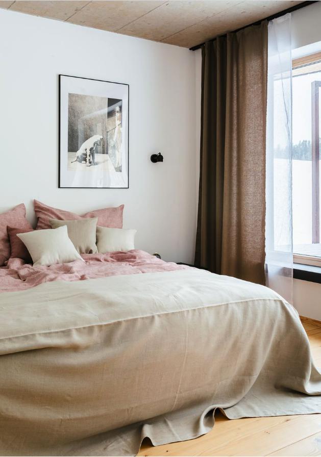 Bett mit Leinen Bettwäsche, weiße Wand mit Bild