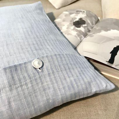 Kopfkissen mit Bezug aus Leinen neben aufgeschlagenem Buch