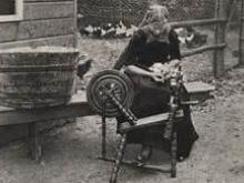 Dame spinnt Garn mit Leinen Spinnrad