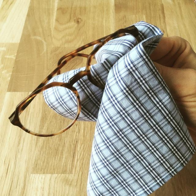 Brille die mit Brillenputztuch aus Baumwolle geputzt wird